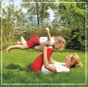 woman playing on grass with kids