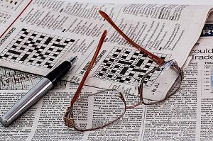 crossword puzzle, pen and glasses