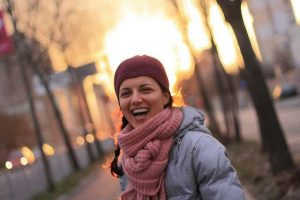 smiling woman with knit scarf and hat