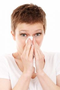 women blowing her nose in a tissue