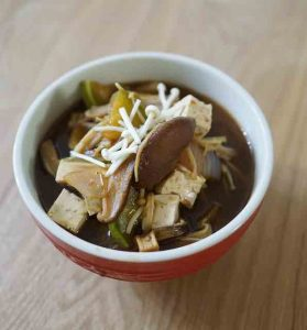 bowl of miso soup with tofu and mushrooms