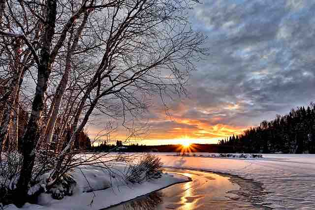 winter landscape with dormant trees, snow, river and sunset