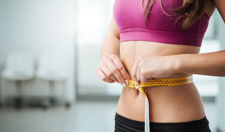 woman measuring stomach with tape measure