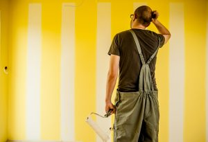 man scratching head with paint roller