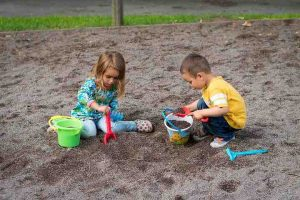 boy and girl playing in sandbox with pails and shovels