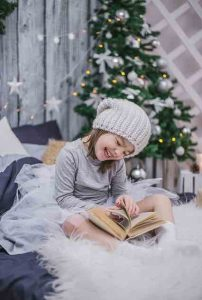 young girl with knit hat in front of christmas tree laughing with book