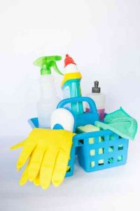 basket of cleaning supplies gloves spray bottles